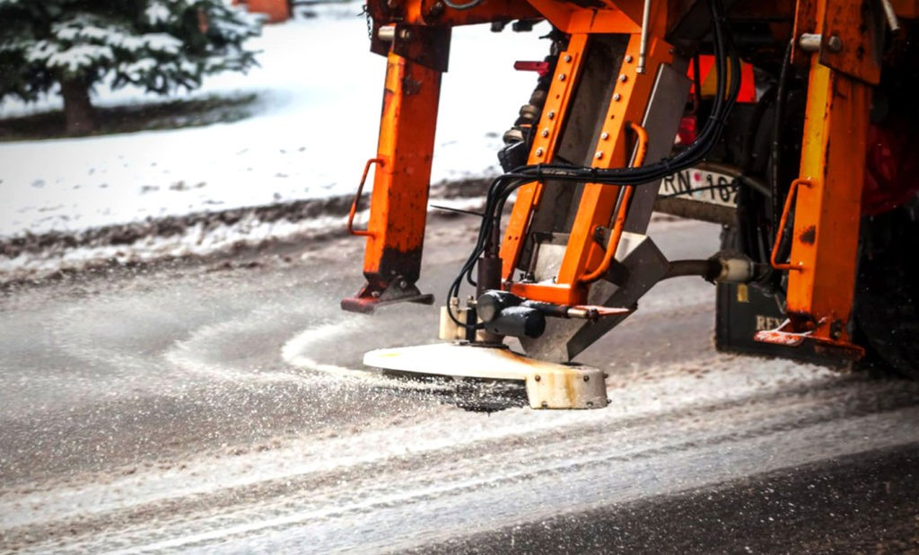 Дорожные покрытия посыпают солью, песком или обрабатывают реагентами