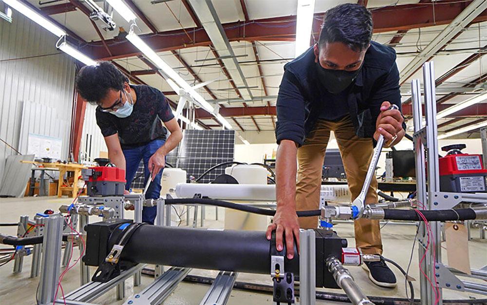Инженеры настраивают поршневой резервуар - ключевой компонент системы