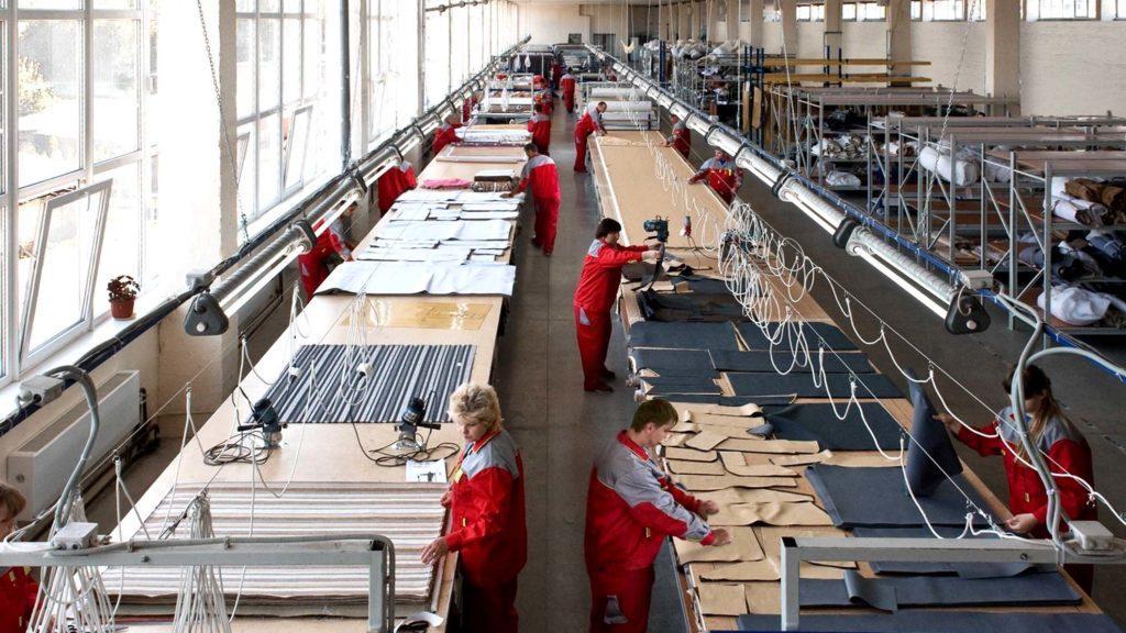 Рабочий процесс на швейной фабрике. Работники пользуются оборудованием, но принимают непосредственное участие в производстве